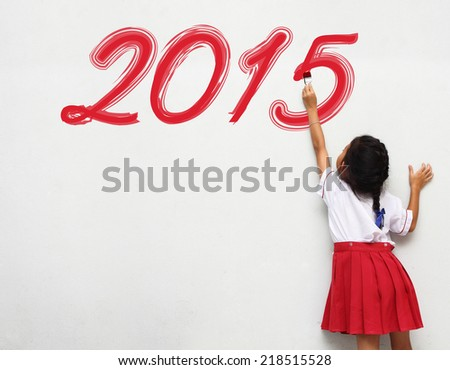 Little girl write the happy new year 2015 - stock photo