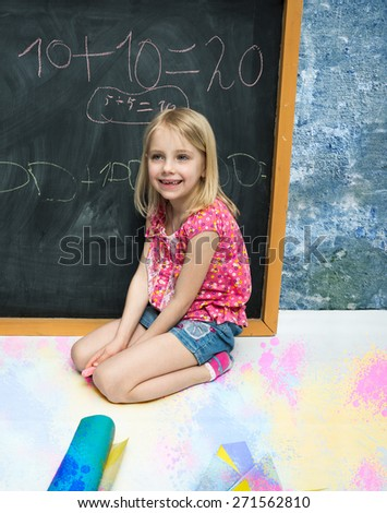 Little girl writes on the blackboard - stock photo