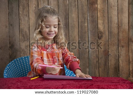 little girl writing a letter , wooden background