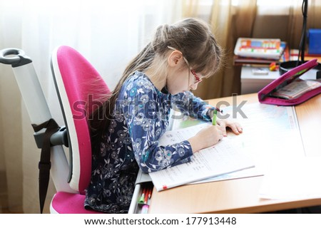 Little girl writing her homework at the desk in her room - stock photo
