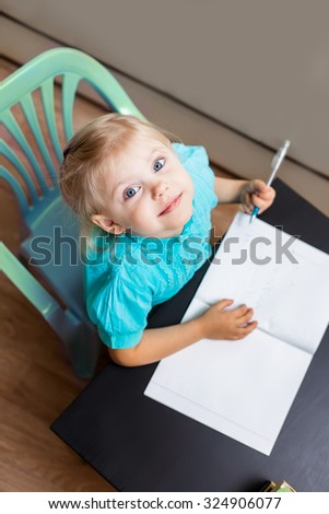 little girl writing in a notebook and smiling. top view
