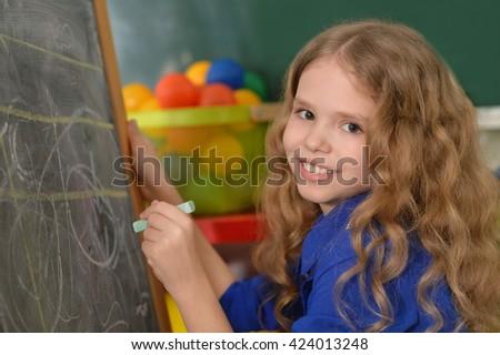 Little girl writing on chalkboard - stock photo