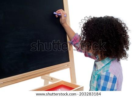 Little girl writing on classroom chalkboard - stock photo