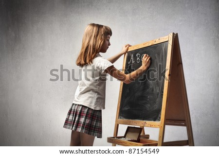 Little girl writing the alphabet on a blackboard