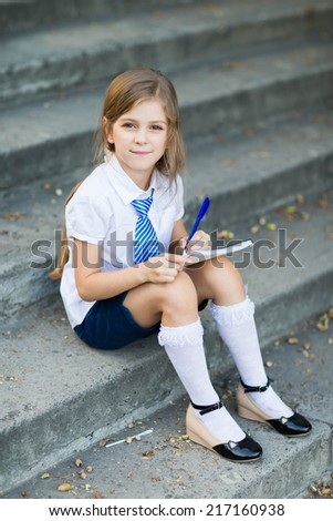 Little girl writting in exercise book in the park - stock photo