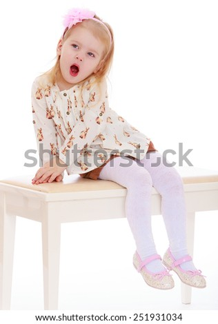 little girl yawns while sitting on the couch.Isolated on white background, Lotus Children's Center. - stock photo