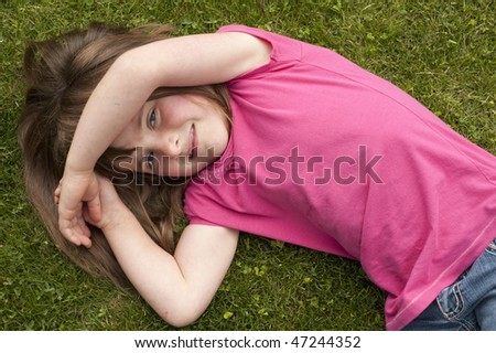 little girl (5 years old) laying in the grass