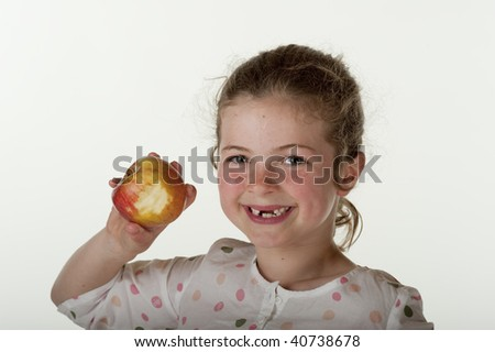 little girl (7 years old) who is missing front teeth eating apple on red bean bag chair against white ibackground