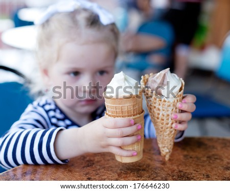 little girl, 3 years old, with blond hair eating ice cream in a cafe - stock photo