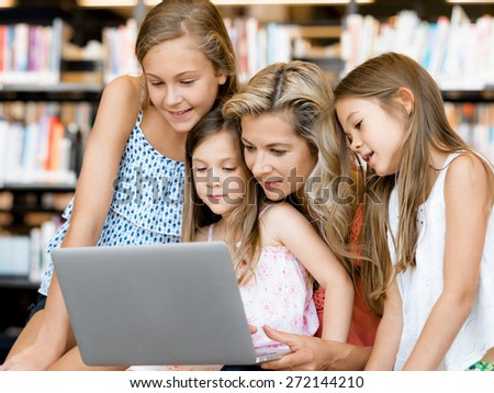 Little girls and mother with a laptop in library - stock photo