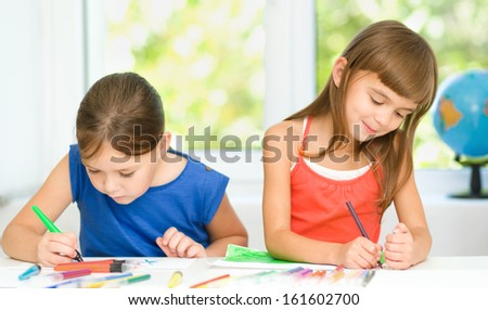 Little girls are drawing using color pencils while sitting at table - stock photo