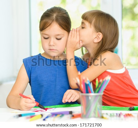 Little girls are drawing using felt- tip pens and gossiping - stock photo