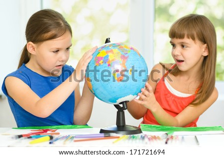 Little girls are examining globe while sitting at table - stock photo