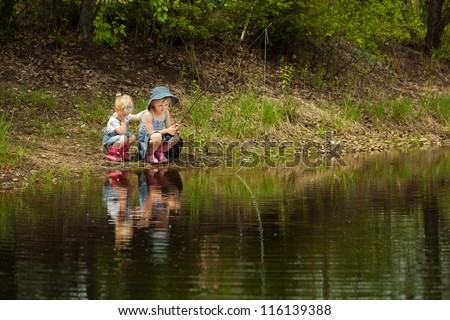 Little girls are fishing on lake in forest - stock photo