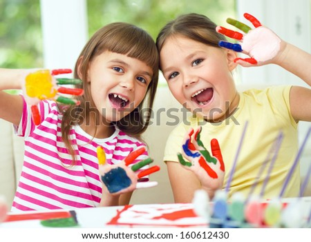 Little girls are painting with gouache and showing their painted hands while sitting at table - stock photo