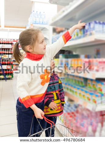 Little girls   choosing   products in   supermarket.