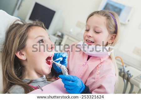 Little Girls Dentist and Patient During Dental Examination. Girl Pretending to be a Dentist is Examining Teeth of another Girl. Funny and Playful representation of Dentist and Dental Theme. - stock photo