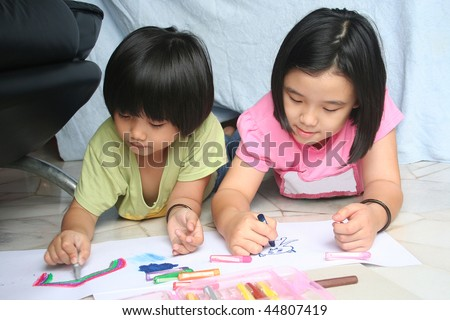 Little girls doing art painting at home together