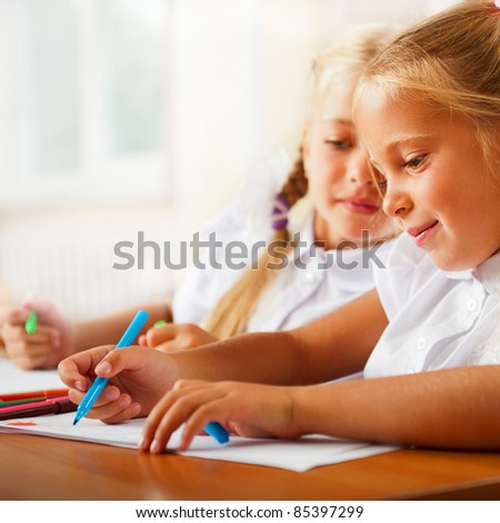 Little girls drawing pictures and writing letters to Santa Claus to get christmas gifts. Indoor at classroom - stock photo