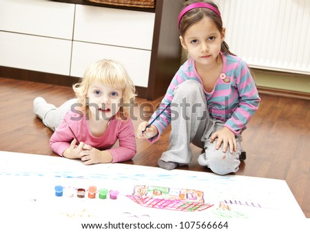Little girls drawing pictures to Santa Claus to get christmas gifts. Indoor at home - stock photo