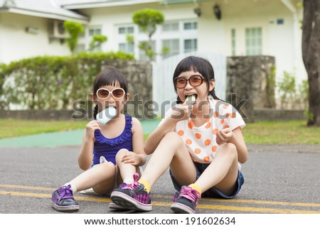 little Girls  Eating Ice Cream and sitting before their house - stock photo