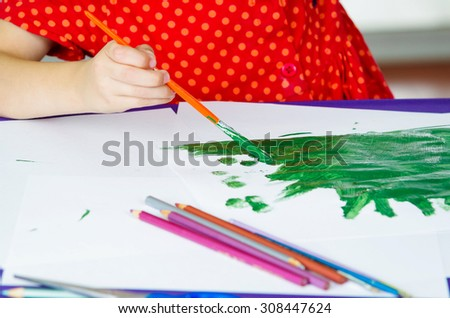 Little girls' hands holding paint brush painting - stock photo
