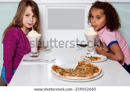 Little girls having a nice time in restaurant - stock photo