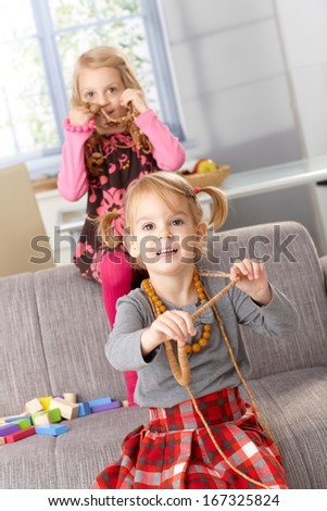 Little girls having fun at home, trying on mother's necklaces, smiling.