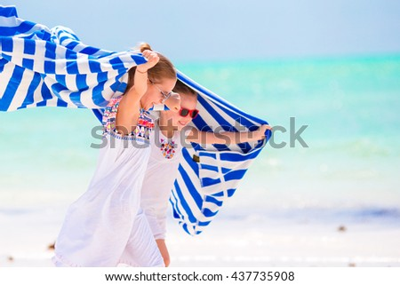 Little girls having fun running with towels on tropical beach. Kids enjoy their family summer vacation in the Indian Ocean - stock photo