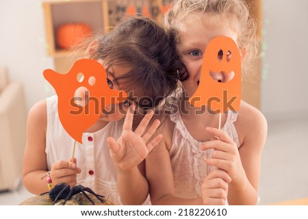 Little girls hiding faces behind paper ghosts - stock photo