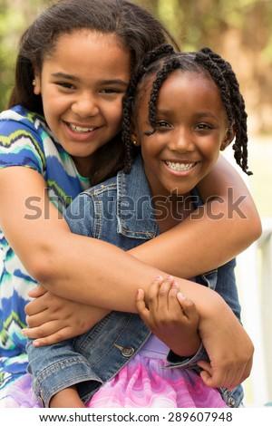 Little girls hugging. Best friends. - stock photo