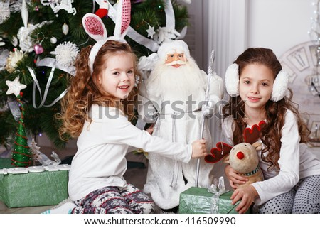 Little girls in comfortable home clothes sitting on floor in beautiful Christmas decorations. Two little sisters decorating Christmas tree with fir-cone. New year preparation. Happy girls and family. - stock photo