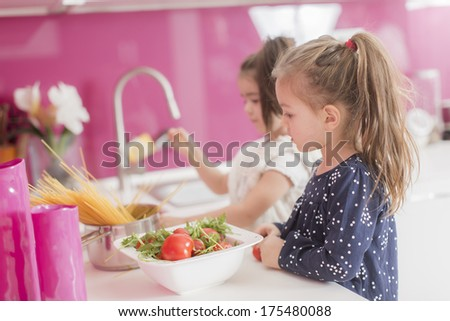 Little girls in the kitchen - stock photo