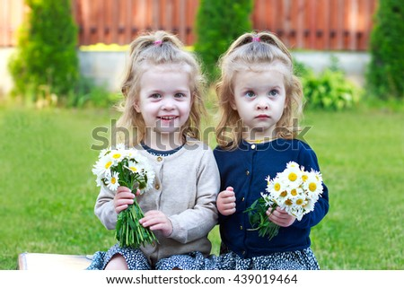 little girls laughing and holding a bouquet of daisies - stock photo