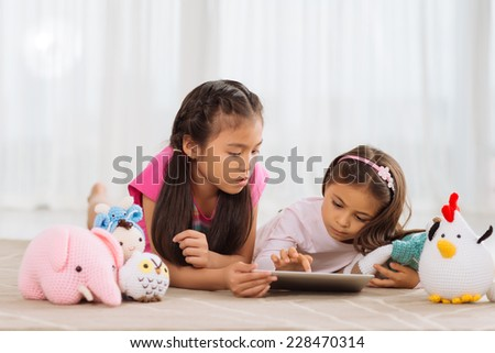 Little girls lying on the floor and playing with knitted toys and digital tablet  - stock photo
