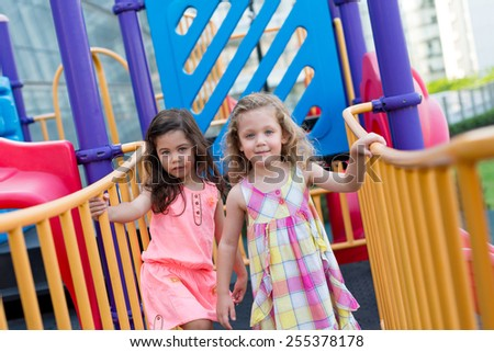 Little girls playing at the playground - stock photo