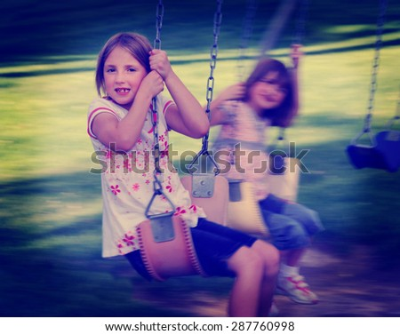 Little girls playing on swing set at a park instagram style - stock photo