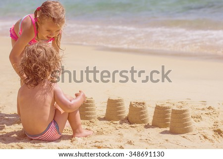 Little Girls Playing on the beach sand at the Aegean Sea.