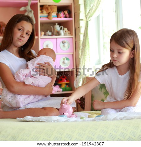 Little girls playing with her baby doll and pretending mom