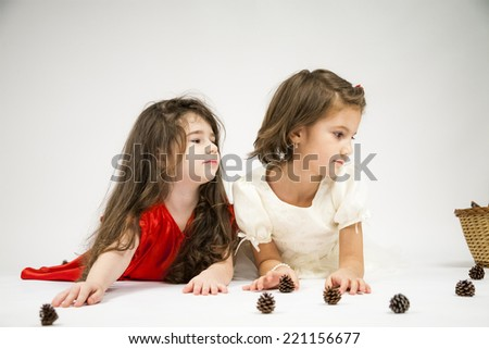 Little girls playing with pine cones and wicker basket on light grey background