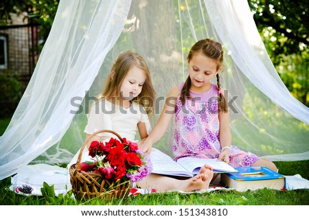 Little girls reading a book together in the park under the canopy - stock photo