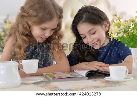 Little girls reading a magazine