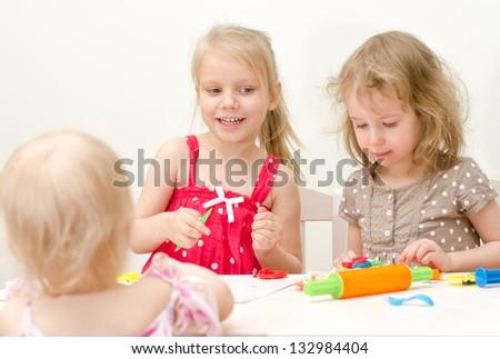 Little girls sculpting using plasticine - stock photo
