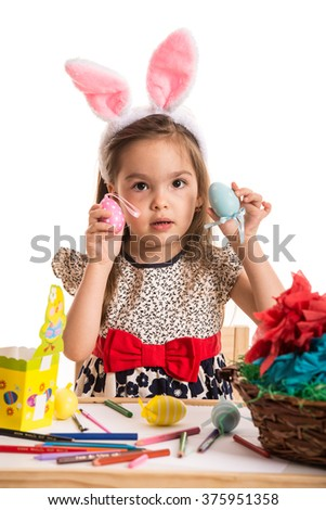 Little girls showing colorful Easter eggs  in front of white background - stock photo