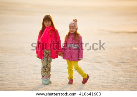 little girls sisters hugging and holding hands in nature. children on the frozen lake