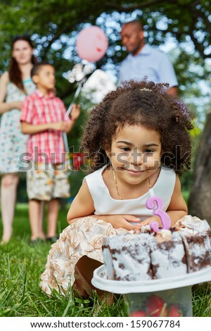 Little girls sits squatted and look at birthday cake, her family stands behind her back not in focus