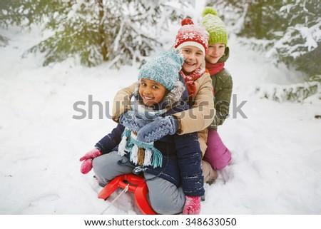 Little girls sitting on sledge in winter park - stock photo