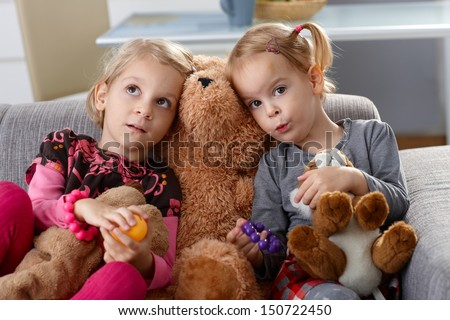 Little girls sitting on sofa with teddy bear between them.