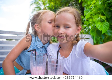 Little girls taking selfie and drinking tasty cocktails at outdoor cafe