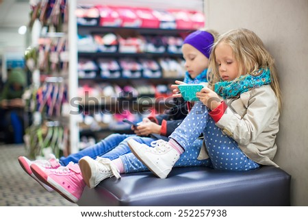 Little girls tired while doing shopping in shopping center - stock photo